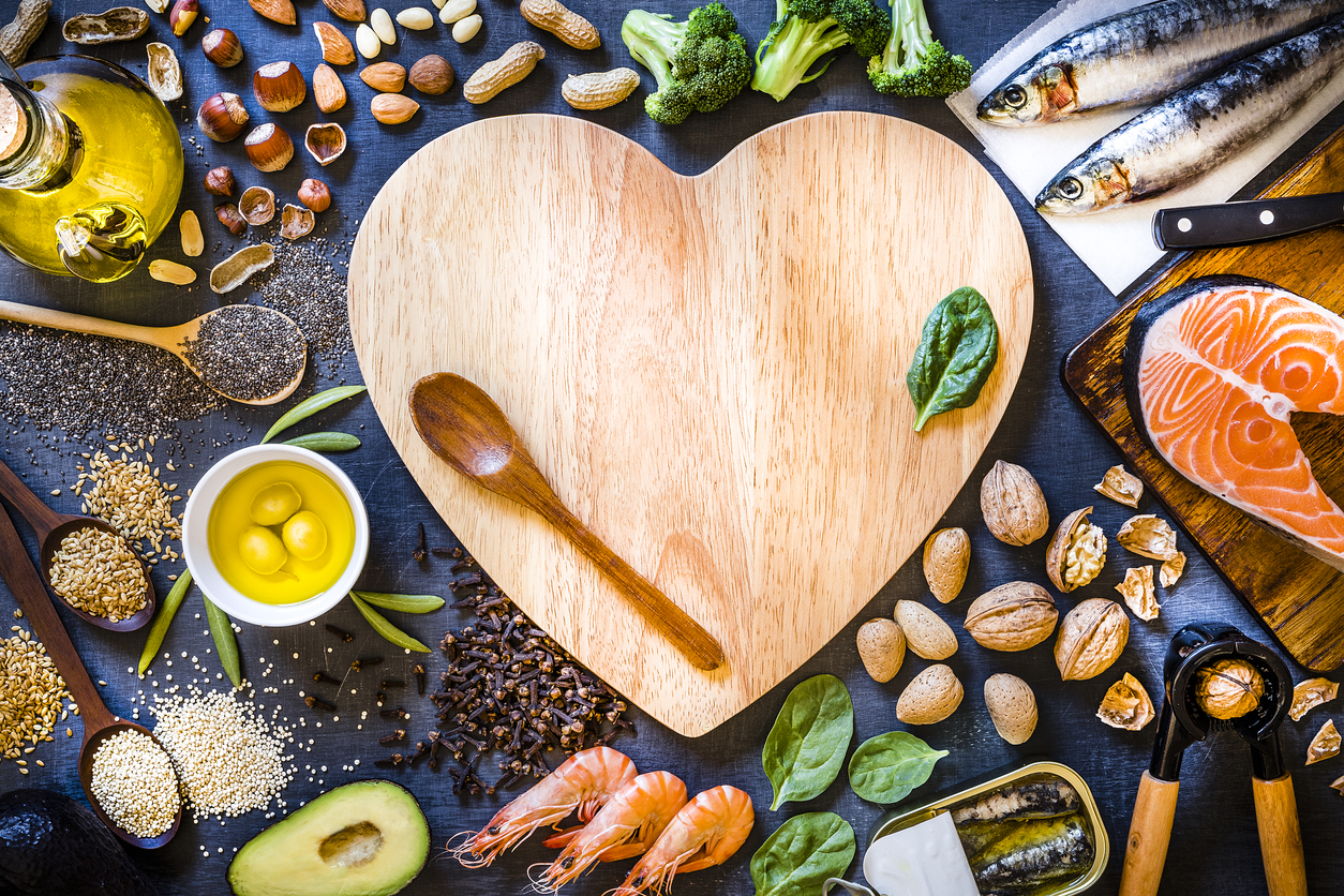 heart shaped cutting board surrounded by heart healthy food